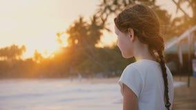 Feliz relaxado pouco 6-8 anos de menina idosa com o cabelo que funde nos suportes do vento que olha ondas do por do sol na praia  video estoque