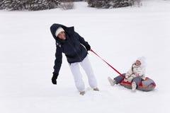 ` Feliz s de la madre que intenta levantarse a la hija de la colina que se sienta en sno Fotos de archivo
