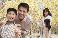 Feliz, sonriendo parents con dos niños que gozan del parque en primavera y que miran las flores Imágenes de archivo libres de regalías