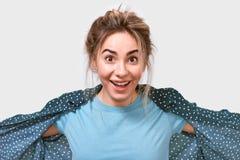 Feliz sorprendió a la mujer hermosa joven en camiseta azul, sonriendo ampliamente, pareciendo alegre y excitado a la cámara imagen de archivo libre de regalías