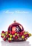 Feliz texto de los chrsitmas y bola roja de Navidad Foto de archivo