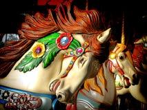 Feliz va la cabeza de caballo adornada carrusel de la ronda Imagen de archivo libre de regalías