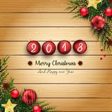 2018 Felizes Natais e o ano novo feliz com bolas e abeto vermelhos ramificam no fundo de madeira ilustração stock