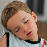 Fell asleep. Young boy fell asleep outdoor on the chair,resting head on his shoulder Royalty Free Stock Photos