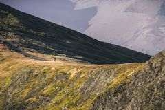 A fell or mountain runner running along mountain side in Lake District, Cumbria, UK royalty free stock photo