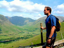 Fell Walker, Wasdale, Cumbria. A fell walker admires the view of Wasdale valley with Kirk fell, Pillar and the slopes of Yewbarrow in the background at Cumbria Royalty Free Stock Image
