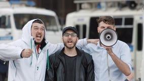 Feller för tre fotboll på bakgrund av polisbilen Pojkar ropar in i en megafon arkivfilmer