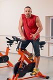 Fellow bycicle cycling in gym Royalty Free Stock Photos
