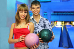 Fellow and girl stand with balls for bowling. Fellow and girl stand alongside with balls for bowling during rest in club, focus on girl Stock Image