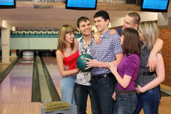 Fellow holds ball and friends stand alongside. One fellow holds ball for bowling and his friends stand alongside with him and all look at him, focus on man in royalty free stock photography