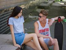 A beautiful girl speaking with a fellow with a longboard sitting on stone stairs on a natural blurred background. Royalty Free Stock Image