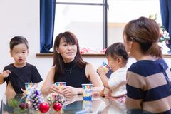 Fellow mom in Japan having food party with their children in the living room at home. Japanese mothers and their kids talking at the party royalty free stock image