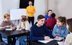 Fellow students having group work tasks during school day. Diligent glad positive fellow students having group work tasks during school day stock photos