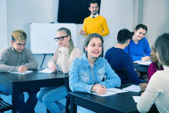 Fellow students having group work tasks during school day. Diligent smiling fellow students having group work tasks during school day stock images