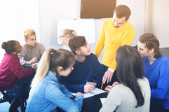 Fellow students having group work tasks during school day. Glad fellow students having group work tasks during school day stock image