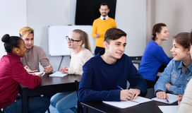 Fellow students having group work tasks during school day. Glad smiling positive fellow students having group work tasks during school day stock photo