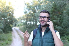 Fellow tourist calling by phone phone in the forest royalty free stock photography