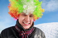 Fellow in wig of clown stands and smiles Stock Images