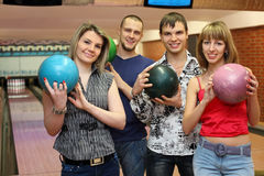 Fellows and girls stand hold balls for bowling. Two fellows and two girls stand in club and hold balls for bowling, focus on fellow on left Royalty Free Stock Photos