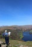 Fellwalker с картой на Loughrigg смотрит к Grasmere Стоковое Изображение RF