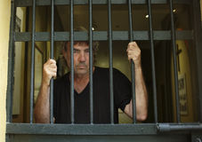 Felon in prison behind bars Stock Photos