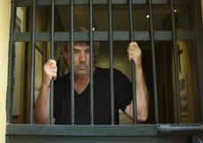 Felon in prison behind bars stock photos
