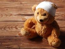 Felpa Brown Teddy Bear con vendado en la tabla imagen de archivo