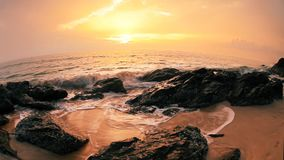 Felsen am aktuellen Strand bei schönem Sonnenuntergang stock footage