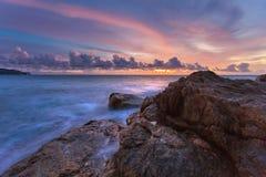 Felsen am aktuellen Strand bei schönem Sonnenuntergang stockbild