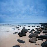 Felsen auf dem Strand auf bewölktem Morgen Stockfotografie