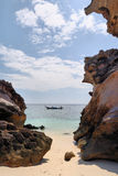 Felsen auf dem Strand, Boot auf dem Meer jenseits Lizenzfreies Stockbild