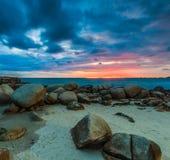 Felsen auf dem Strand im Sonnenuntergang Lizenzfreie Stockfotos