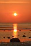 Felsen auf dem Strand mit rotem Sonnenuntergang Stockbilder