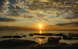 Felsen auf dem Strand mit Sonnenunterganghimmel Lizenzfreies Stockbild