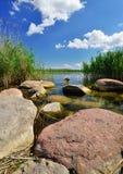 Felsen auf dem Ufer des Sees. Stockbilder