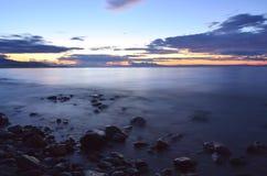 Felsen auf dem Ufer des Sees bei Sonnenuntergang Stockbilder
