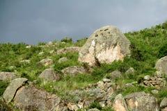 Felsen auf einem grünen Hügel bei Sonnenuntergang vor Regen Lizenzfreie Stockbilder