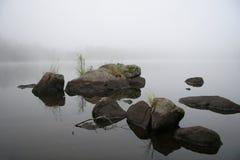 Felsen auf Nebel hüllten See ein Stockfotos