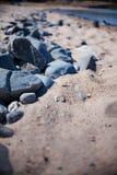 Felsen auf sandigem Strand Stockbild