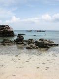 Felsen auf Strand mit Booten Lizenzfreie Stockfotografie