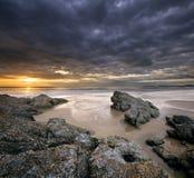 Felsen auf Strand mit drastischem Himmel Stockbild