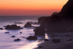 Felsen deckte Kalifornien-Strand am Sonnenuntergang ab Stockfotos