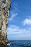 Felsen, der vertikal aus dem Wasser heraus haftet Stockfotografie