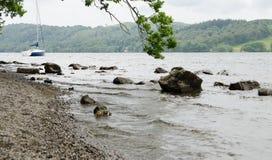 Felsen, die über das Wasser von einem stürmischen See Windermere steigen stockfotografie