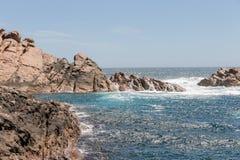 Felsen durch die Küste im dunkelblauen Wasser Stockbilder