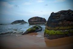 Felsen durch Strand Stockbild