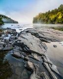 Felsen in einem Fluss bei Sonnenaufgang im Nebel stockfoto
