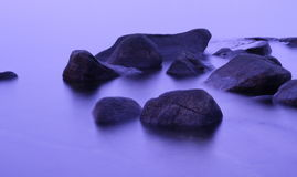 Felsen in einem purpurroten nordischen Wintermeer Lizenzfreies Stockbild