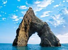 Felsen in Form eines Bogens im Meer Stockbild