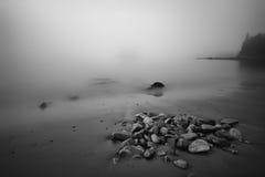 Felsen gestreute Küsten-Maine Beach im dichten Nebel Stockfotografie